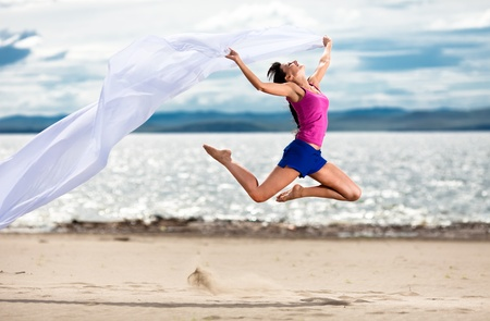 Beautiful young woman jumping on the beach with a white tissue  photo