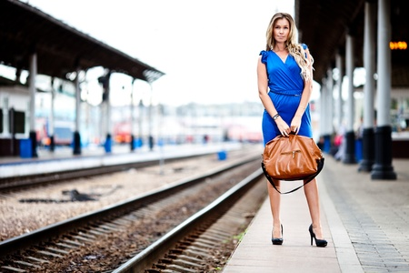 baggage train: attractive lady waiting train on the platform of railway station  Stock Photo