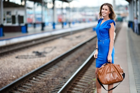attractive lady waiting train on the platform of railway station  photo