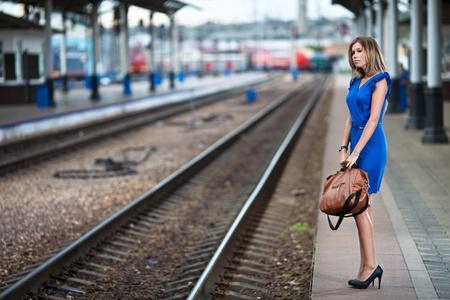 entrenar: Dama atractiva espera tren sobre la plataforma de la estaci�n de ferrocarril