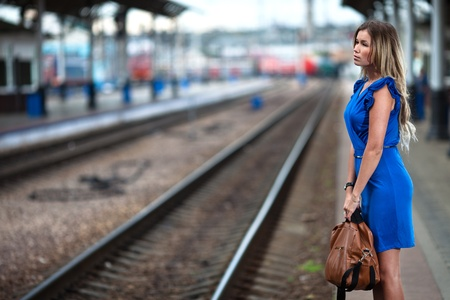 old train: attractive lady waiting train on the platform of railway station  Stock Photo