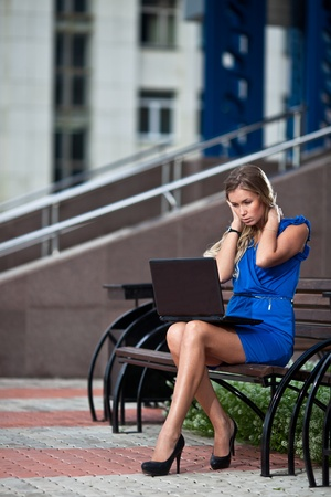 attractive stylish lady with laptop sitting on a bench in the city photo
