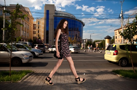 young carefree woman walking at the street in city photo