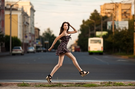 dress shoe: young carefree woman jumping at the street in city Stock Photo