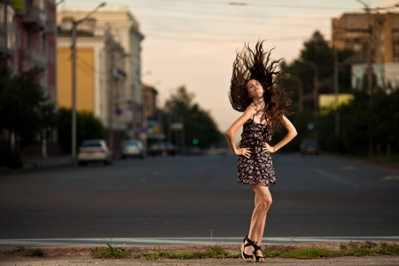 Fashion young woman posing at the city photo