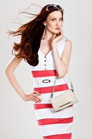 red purse: Beautiful sexy caucasian woman in stylish dress. Studio shot