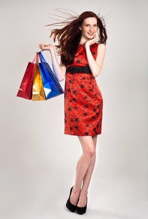Beautiful sexy caucasian woman in stylish dress with shopping bags photo