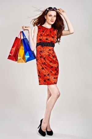 Beautiful sexy caucasian woman in stylish dress with shopping bags photo