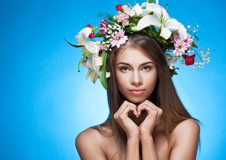Hermosa mujer con corona de flores. Espacio para el texto.