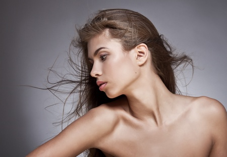 clavicle: Beautiful woman with fluttering hair. On dark background.