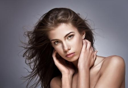main sur l epaule: Belle femme avec bruissements de cheveux. Sur un fond sombre.  Banque d'images