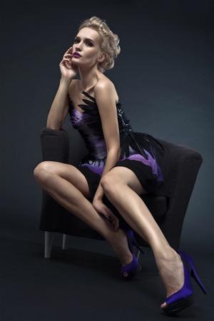 La imagen de una hermosa mujer sentada en una silla de lujo. Foto de estudio