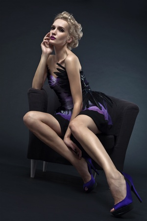 The image of a beautiful luxurious woman sitting on chair. Studio shot Stock Photo - 10487663