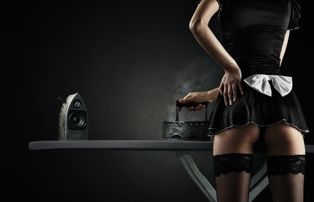 erotic: Vintage sexy maid with iron audio speakers on black background