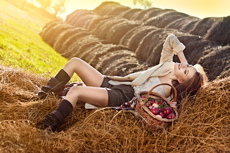 haystack: beautiful smiling woman with many apple in basket on haystack at farm