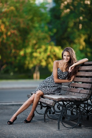 Magnificent brunette sits on bench which is on city street photo