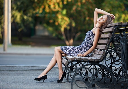 sits: Magnificent brunette sits on bench which is on city street