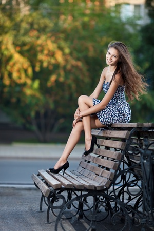 shoe model: Magnificent brunette sits on bench which is on city street