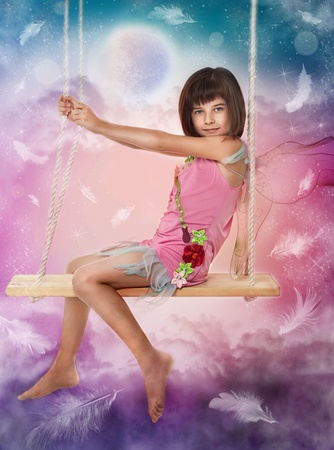 magic young: Little girl sitting on the swing  Stock Photo