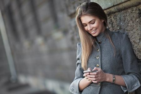 amigas conversando: Mujer, sonriente, el env�o de sms en la calle