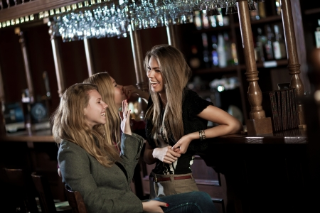 night club interior: Three happy young women in a nightclub sitting at the bar Stock Photo
