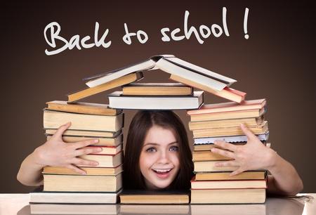 La muchacha adolescente con un mont�n de libros en todo, volver a la escuela