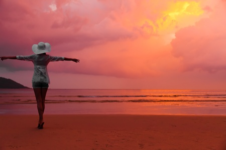 Young woman in hat standing on wet sand and looking to red sunset sky  photo
