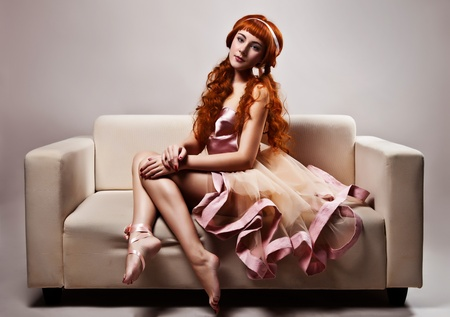 The image of a beautiful woman in luxurious dress sitting on sofa. Studio shot  photo
