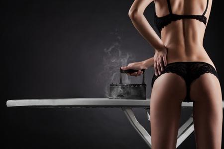 sexy woman with  retro iron on black background Stock Photo