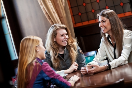 coffee houses: pretty girl-friends talk and drink coffee in cafe house Stock Photo