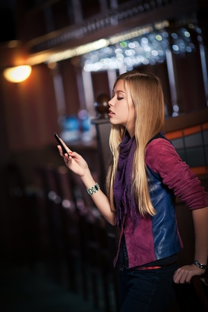 young woman sending sms on smartphone in the interior of the bar  photo