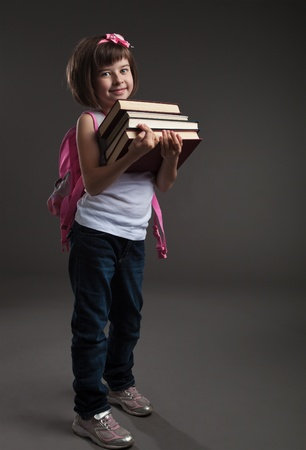 Portrait of a cute small girl going to school. Studio shot photo