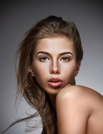 Hermosa mujer con brillante maquillaje. El fondo oscuro.