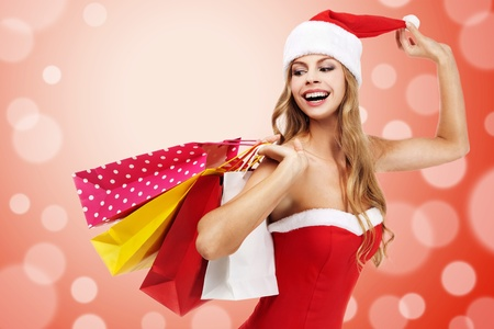 Charming woman in santa costume holding a shopping bags over red background  Stock Photo - 11590880