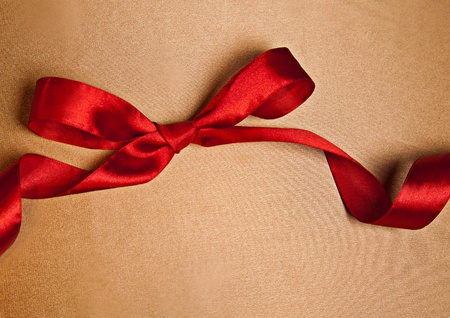 Shiny red satin ribbon on golden background with copy space photo