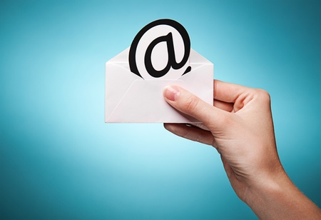 womans hand holding an envelope with a sign of the e-mail against blue background photo