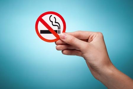 vrouw hand die een symbool - niet roken. Tegen een blauwe achtergrond
