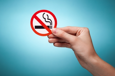 womans hand holding a symbol - no smoking. Against blue background photo