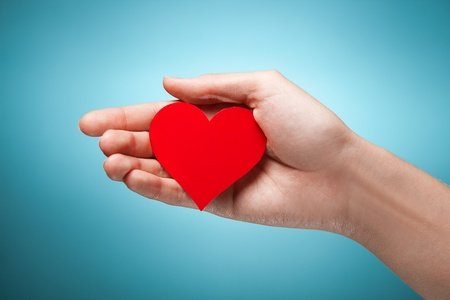 womans hand holding symbol - red heart. Against blue background photo