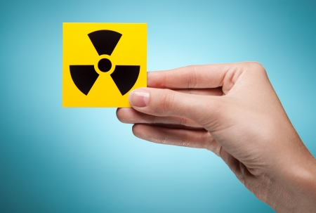 woman's hand holding symbol - radiation. Against blue background Stock Photo - 11590979