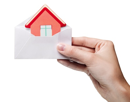 housing estate: womans hand holding an envelope with a sign of the house isolated Stock Photo