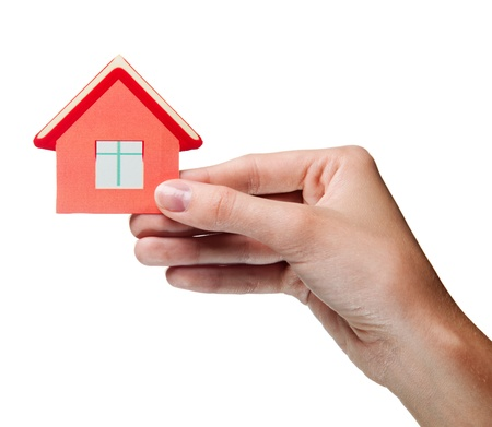 woman's hand: womans hand holding sign of the house. Isolated Stock Photo