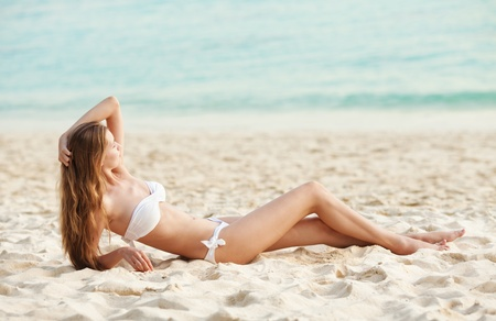 Beautiful woman sunbathing on the tropical beach photo