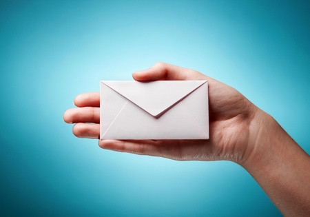 woman's hand holding closed envelope against blue background Stock Photo - 11591024