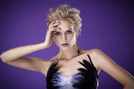 The image of a beautiful luxurious woman on purple background. Studio shot  photo