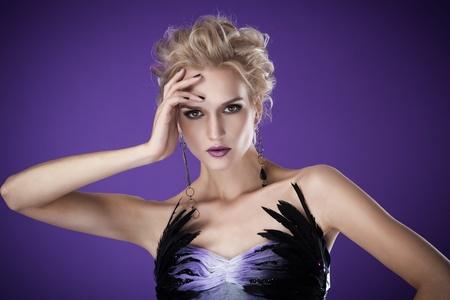 The image of a beautiful luxurious woman on purple background. Studio shot  photo