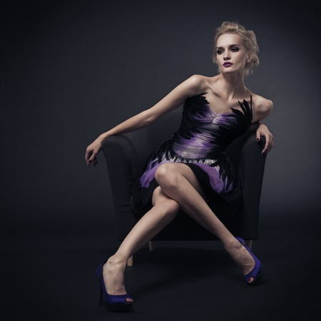 The image of a beautiful luxurious woman sitting on chair. Studio shot  Stock Photo