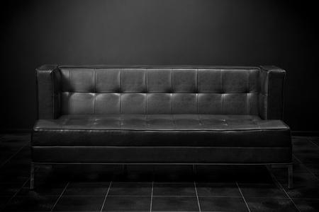 Old black sofa in dark room photo