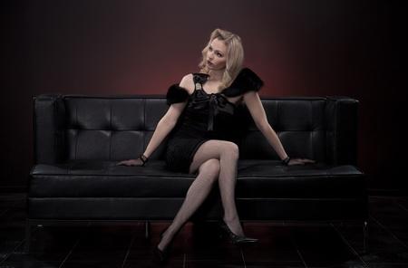 Beautiful retro woman on black sofa photo