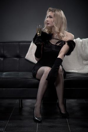 Beautiful retro woman with champagne on black sofa  photo
